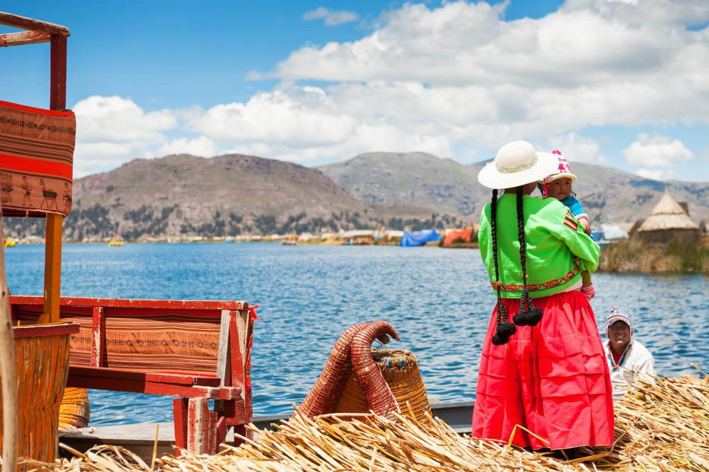 Picture of a lady watching over Lake Titicaca with her children.