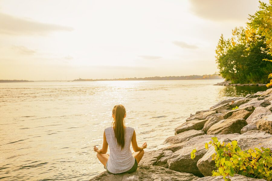 A girl sat beside a lake, practicing mindfulness in South America.
