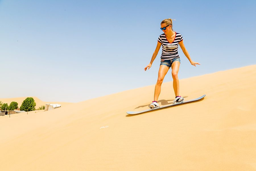 A picture of a lady sandboarding in South America.