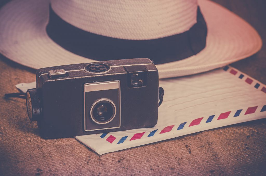 A picture of a retro camera and tourist hat.