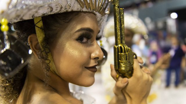 A picture of a female dancer with a toy gun at the rio carnival.
